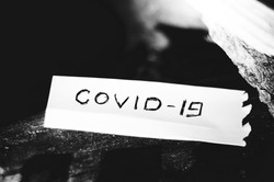 Historic vanquished COVID-19 virus written on a piece of paper. Black and white photography.