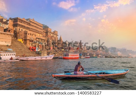 Historic Varanasi city architecture at sunset with view of a boatman rowing on river Ganges
