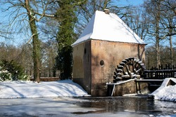 Historic water mill at riverside with snowlandscape. Scenic travel destinations in the netherlands. Old hydro power construction. water managment building.