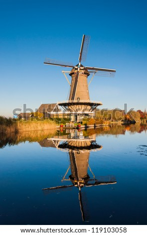Historic windmill in the Netherlands reflected in a mirror smooth water surface of the river.