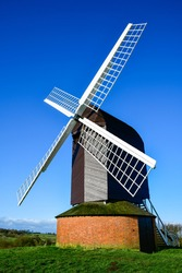 Historic windmill: Old wood and brick windmill on a hilltop. Popular heritage and tourist site. English countryside background.