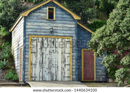 Historic wooden boat shed with paint peeling off weathered walls. #1440634100