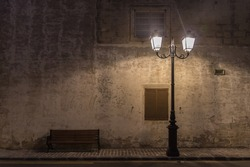 Historical ancient street Lamp and a bench at night with the wall behind them on the old stony pavement on the road with yellow lines