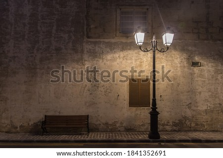 Historical ancient street Lamp and a bench at night with the wall behind them on the old stony pavement on the road with yellow lines Photo stock ©