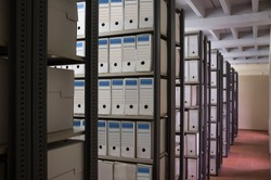 Historical archive warehouse full of carton boxes. Shelves perpective shot