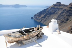 Historical boat on top of the roofs at Santorini
