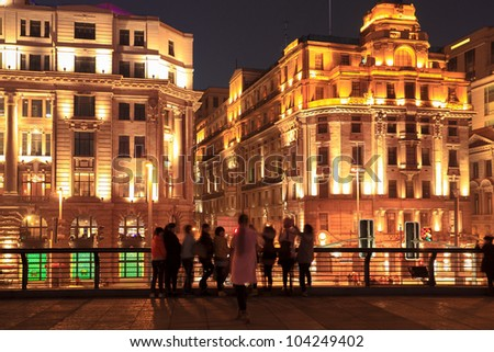 historical buildings in shanghai bund at night with tourists
