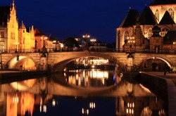 Historical center of Ghent, Belgium night panorama. Medieval bridge and medieval Ghent castle with reflections in water
