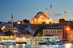 Historical center of Istanbul in evening, Turkey. Tourist ships docked in harbour of Istanbul at night. View of old Istanbul with large illuminated mosque at dusk. Traveling and vacation in Istanbul.