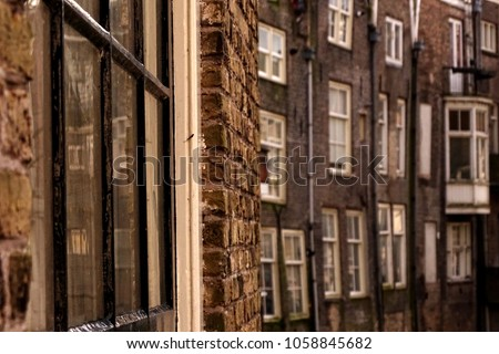Historical curve tenement houses in netherlands. Windows reflect surrounding enviroment. In foreground zommed ans sharp black vintage window. Bricks all around. In background white frames. gold filter