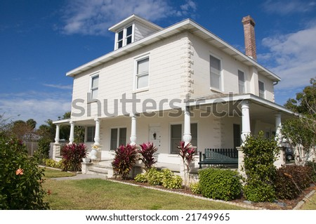 historical home with unique porch pillars with blue sky stock photo