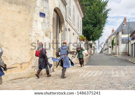 Historical reconstruction: medieval knights fighting with swords in the castle walls of Chateaudun. Ancient fortification, battle, warriors, soldiers.