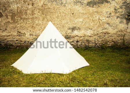 historical reconstruction medieval white tent on green grass meadow near ancient stone castle wall with empty space for copy or text