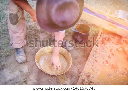 Historical reconstruction work vintage prospector. Flushing gold in the tray in America in Alaska.. Gold miner cleans gold by hand in the copper pan.