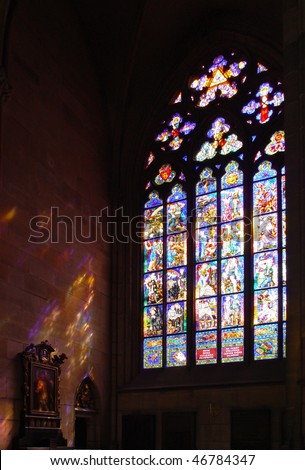 Historical stained glass window with religious scene and reflection on  wall and icons