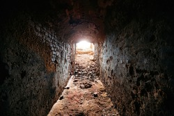 Historical underground red brick passage. Light at the end of tunnel
