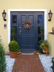 historical wooden front door decorated with garland