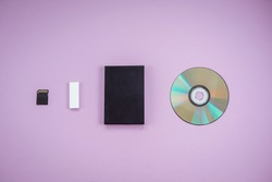 history of data storage devices on a lilac background. dvd, flash drive, hard drive, sd card top view