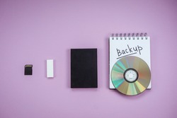 history of data storage devices on a lilac background. dvd, flash drive, hard drive, sd card top view. Notepad backup text