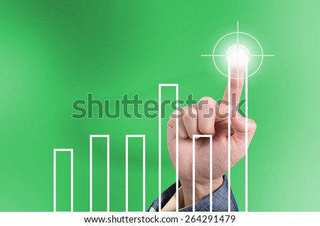 Hit the target, business concept with finger touching top bar chart on a virtual touch screen