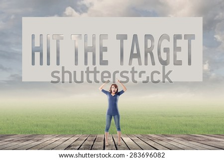 Hit the target, words on blank board hold by a young girl in the outdoor.