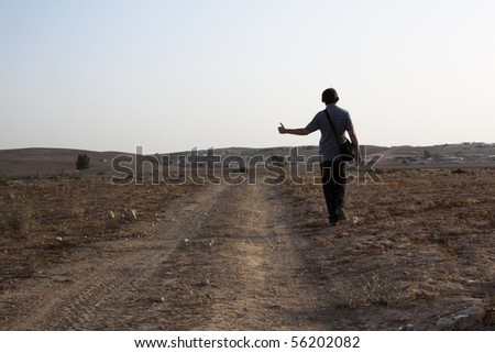 hitchhicker walkin by a road in a desert