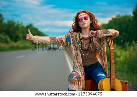 Hitchhiking girl. Beautiful hippie girl standing on a highway and catching a passing car. Spirit of freedom. Fashion shot. Bohemian, bo-ho style.