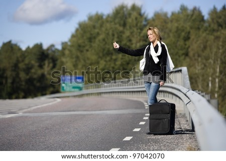 Hitchhiking woman alone at the side of the road - stock photo