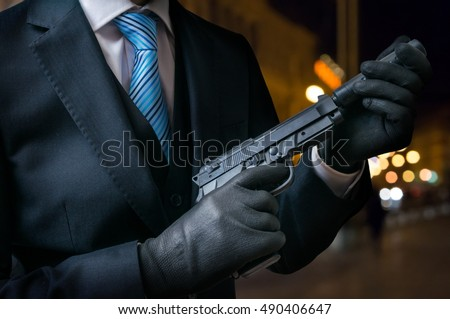 Stock Photo Hitman or assassin holds pistol with silencer in hands.