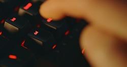 Hitting delete button on illuminated keyboard closeup