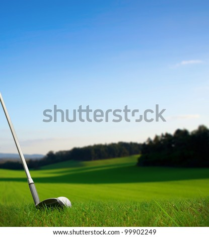 hitting golf ball with club along fairway towards green