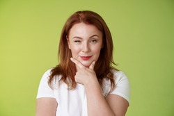 Hmm interesting choice. Intrigued cunning redhead middle-aged female hold hand face-line rub chin thoughtful smirking pleased raise eyebrow curious pondering alluring decision green background