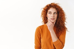Hmm interesting. Curious cunning good-looking redhead girl planning perfect scheme, rub chin, squinting suspicious and thoughtful peek left, thinking, pondering between nice choices