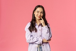 Hmm interesting. Portrait of smiling creative girl in denim jacket, thinking, have intriguing idea, smirk and look upper left corner, daydreaming, planning something for party, pink background