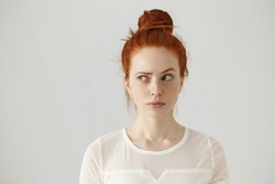 Hmm. Let me think. Studio shot of cute redhead girl with hair knot and freckles looking sideways with thoughtful and sly expression, raising one brow as if having good idea, planning something