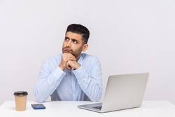 Hmm, need to think! Pensive thoughtful businessman sitting office workplace with laptop on desk, pondering business plan, having doubts, not sure. indoor studio shot isolated on white background