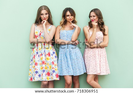 Hmm. Not sure. Three cheerful girl planning something and playfully looking at camera. Isolated on green background, studio shot