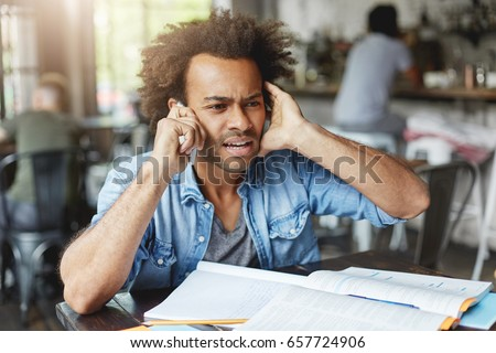 Hnadsome dark-skinned college student dressed casually looking frustrated, plugging one ear while trying hard to hear what they are saying on the other end of line, asking What? Come again please?