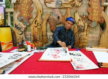 HO CHI MINH CITY, VIET NAM- JAN 19: Vietnamese calligrapher writing calligraphy letter at fair, a traditional ceremony, man in tradition dress, Vietnam, Jan 19, 2014