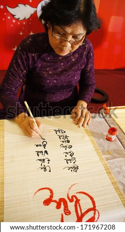 HO CHI MINH CITY, VIET NAM-JAN 15: Woman writing calligraphy, she write vietnamese letter at year end event, calligrapher who have kind face, intellectual wear traditional dress, Vietnam, Jan 15, 2013