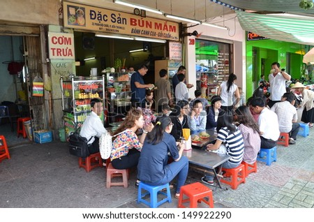 HO CHI MINH CITY, VIETNAM - AUG 3: Customers have their mail on the street stall on August 3, 2013 on Ho Chi Minh City. Vietnamese people love to socialise as they eat.