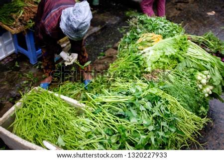 Ho Chi Minh City, Vietnam - January 2 2019: Vegetable seller sorting her produce. #1320227933