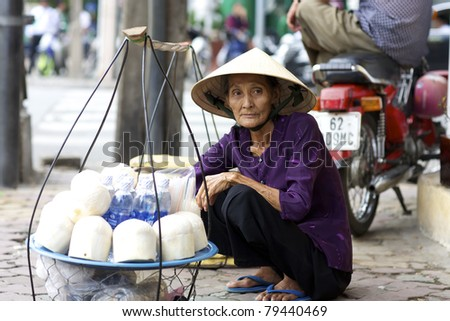 HO CHI MINH CITY, VIETNAM- JUNE 2: Unidentified woman street vendor in Ho Chi Minh City, Vietnam selling coconuts and water on June 2, 2008.  Vietnam produces over 1 million tons of coconuts per year.