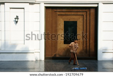 HO CHI MINH CITY, VIETNAM- MAY 12: Young man working on five star hotel lobby, he wear employee uniform, cleaning tile floor, luxury hotel with white wall, wooden door, Saigon, Viet Nam, May 12, 2014