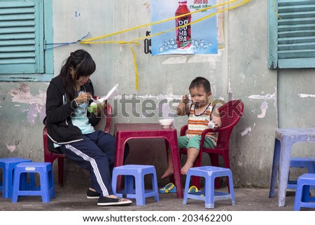 HO CHI MINH CITY,VIETNAM-NOV 5TH2013 : Young girl and boy eating breakfast at a street restaurant. Street restaurants are everywhere in Ho CHi Minh.