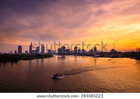 Ho Chi Minh's Panorama view over the Saigon River. Dramatic lighting spectacular sunset is highlighted by a canoe surfing on the water at a faster rate #284085023
