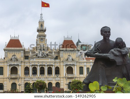 Ho Chi Minh statue and Saigon City Hall with flag. Combination shot of the statue with the chateau-like French-built city hall, the center of power in Ho Chi Minh City.