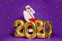 Ho-ho-ho! Full body photo of santa man sit on motorbike big air newyear 2020 balloons saying congratulations wear sun specs x-mas costume isolated purple background