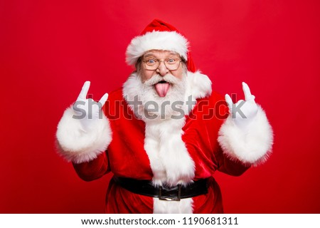 Ho-ho-ho! Party time concept. Aged mature playful emotion grandfather Santa with gloves sticking tongue out and comic grimace fooling around isolated on noel bright red background #1190681311