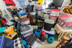 Hoarder room packed with storage boxes, old electronics, files, business equipment and household items.